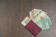 旅行生物统计的护照特写镜头与里面的登舱牌的和捆绑在桃花心木桌上的亚洲金钱 免版税库存照片