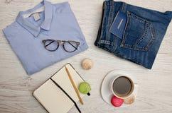 旅行的准备 蓝色衬衣、牛仔裤有护照的,笔记本和咖啡 秀丽蓝色聪慧的概念表面方式构成妇女 免版税库存照片