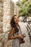 旅行的妇女在她手和微笑上的拿着葡萄酒照相机 免版税库存照片