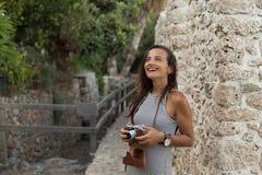 旅行的妇女在她手和微笑上的拿着葡萄酒照相机 免版税库存图片
