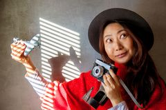 旅行的有趣的背景 女孩拿着飞机,并且照相机在墙壁和微笑附近站立 免版税库存照片