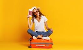 旅行的概念 带着手提箱的愉快的妇女在黄色背景的女孩和护照 免版税图库摄影