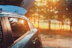旅行的温暖的斜背式的汽车汽车停车处在日落的森林里 免版税库存图片