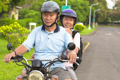 旅行的资深夫妇推进摩托车 库存照片