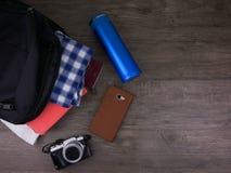 旅行的顶视图项目在黑袋子、大海瓶、手机和照相机包括衣裳在木背景 库存图片