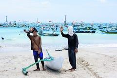 旅行目的地,海岛文化 两地方地方巴厘语渔夫,传统小船 Kelan海滩,巴厘岛,印度尼西亚10月11日 免版税库存图片