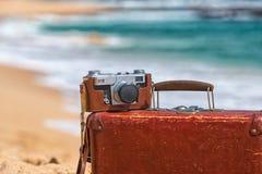旅行葡萄酒手提箱和照相机在海滩 免版税图库摄影