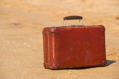 旅行葡萄酒手提箱是单独的在海滩 免版税库存图片