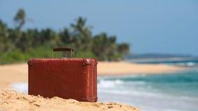 旅行葡萄酒手提箱是单独的在海滩 库存照片