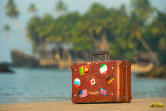旅行葡萄酒手提箱是单独的在海滩 免版税库存照片
