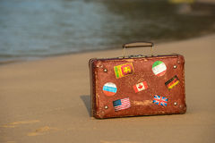 旅行葡萄酒手提箱是单独的在海滩 免版税图库摄影