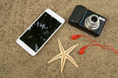 旅行计划和假期的概念在海沙 顶视图智能手机,照相机,海星,耳机 免版税库存照片
