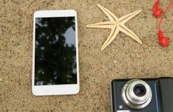 旅行计划和假期的概念在海沙 顶视图智能手机,照相机,海星,耳机 免版税图库摄影