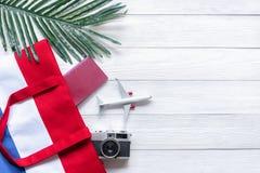 旅行计划 在海滩的旅客计划的旅行暑假与旅客辅助部件、减速火箭的照相机、sunblock和护照 库存照片