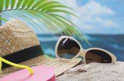 旅行设备、镜片和太阳帽子在海和天空backgrou 免版税图库摄影