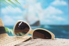 旅行设备、镜片和太阳帽子在海和天空backgrou 免版税库存照片