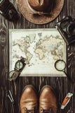 旅行设置顶视图与草帽、地图、鞋子、指南针、放大镜和照片照相机的在黑暗 免版税图库摄影