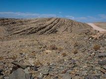 旅行通过岩石山烘干了纳米比亚沙漠多灰尘的风景背景有分裂的页岩片断和其他石头的 免版税库存照片