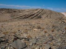 旅行通过岩石山烘干了纳米比亚沙漠多灰尘的风景背景有分裂的页岩片断和其他石头的 图库摄影