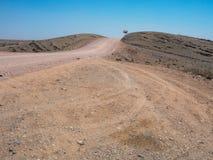 旅行通过有汽车轮胎轨道的粗砺的多灰尘的未铺砌的路通过天旱沙漠气候和岩石山环境美化 免版税库存照片