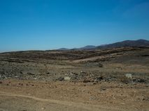 旅行通过有汽车轮胎轨道的粗砺的多灰尘的未铺砌的路通过天旱沙漠气候和硬岩山环境美化 免版税库存照片