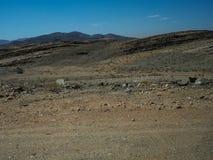 旅行通过有汽车轮胎轨道的艰难的多灰尘的未铺砌的路通过天旱沙漠气候和硬岩山环境美化 免版税库存照片