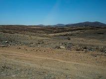 旅行通过有汽车轮胎轨道的艰难的多灰尘的未铺砌的路通过干沙漠气候和硬岩山风景 免版税图库摄影