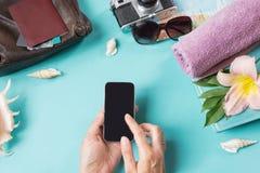 旅行集合、太阳镜和夏天辅助部件在蓝色背景 智能手机在女性手上 在视图之上 空白的嘲笑为a 免版税库存图片