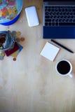 旅行项目个人计算机,电话,太阳镜,金钱,在木后面的咖啡 图库摄影