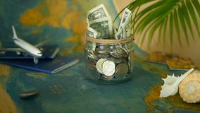旅行预算概念 在玻璃瓶子的假期存的金钱在世界地图背景 股票视频