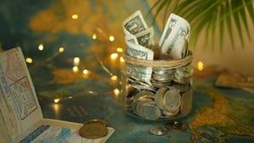 旅行预算概念 在玻璃瓶子的假期存的金钱在世界地图背景 影视素材