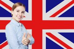 旅行,实习和学会英语语言在英国 有赞许的俏丽的女生反对英国旗子背景 免版税库存照片
