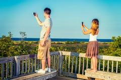 旅行年轻的夫妇,与手机的录影记录 图库摄影