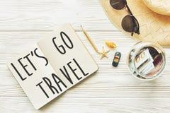 旅行 让` s去旅行文本在空的笔记本的标志概念 Pla 免版税库存图片