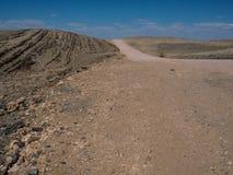 旅行Opyspace通过纳米比亚沙漠干多灰尘的岩石山风景地面有分裂的石和蓝天 库存照片
