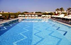 旅馆与太阳懒人的游泳池 免版税库存照片