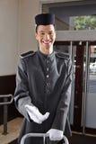 旅馆制服的愉快的看门人 库存图片