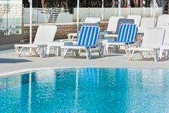 旅馆在游泳池附近的游泳池边椅子 库存图片