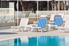 旅馆在游泳池附近的游泳池边椅子 图库摄影
