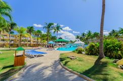 旅馆地面、热带庭院和各种各样的游泳池邀请的看法与人放松 免版税库存图片