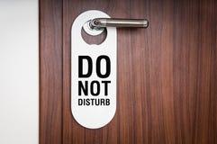 旅馆客房的门有标志的不干扰 免版税库存图片