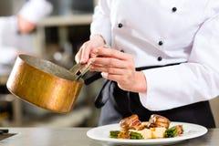 旅馆或餐馆厨房烹调的厨师 免版税库存照片