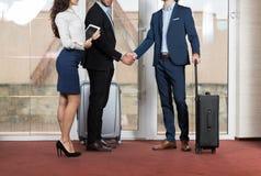 旅馆接待员会议在大厅,两个商人会议握手的商人小组 免版税库存照片