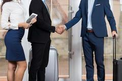 旅馆接待员会议在大厅,两个商人会议握手的商人小组 免版税库存图片