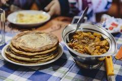 旅馆早餐是土豆与roti的咖喱汤在锡金,印度 免版税库存照片