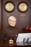旅馆柜台的微笑的女性接待员 免版税库存图片