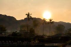 旅馆游泳池、棕榈树、伞和椅子剪影  在日出,软的焦点图片的热带手段 免版税库存照片