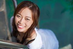 旅馆游泳池松弛假期旅行的亚裔妇女,享用温泉的女孩 免版税库存照片