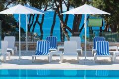 旅馆游泳池边椅子有海视图 库存图片