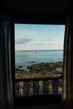 从旅馆窗口的令人愉快的看法向有岩石的海 免版税库存图片